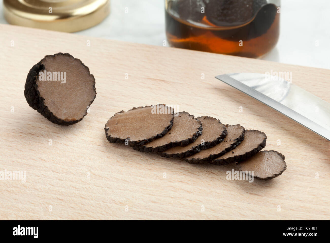 Preserved summer truffle from a pot cut into slices on a cutting board - Stock Image