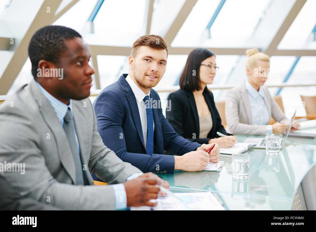 Young businessman looking at camera at conference among other employees - Stock Image