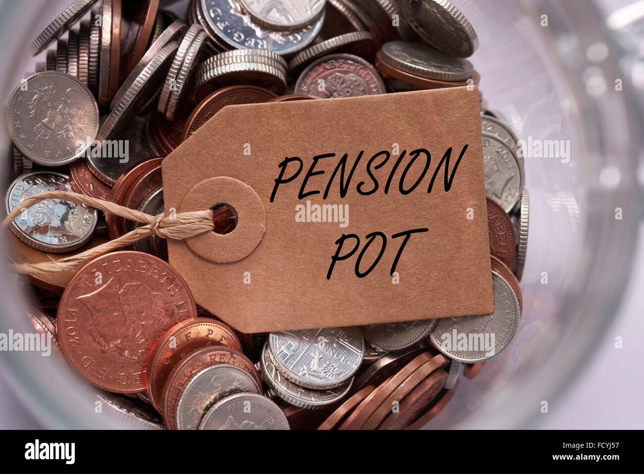 pension pot label on british mixed coins inside a glass jar concept concept - Stock Image