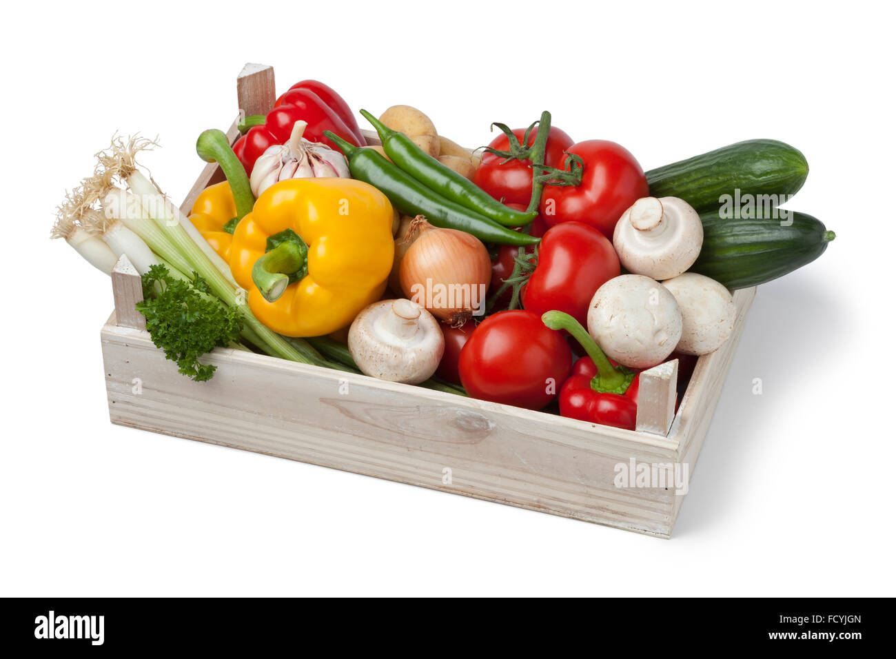 Wooden chest with fresh vegetables on white background - Stock Image