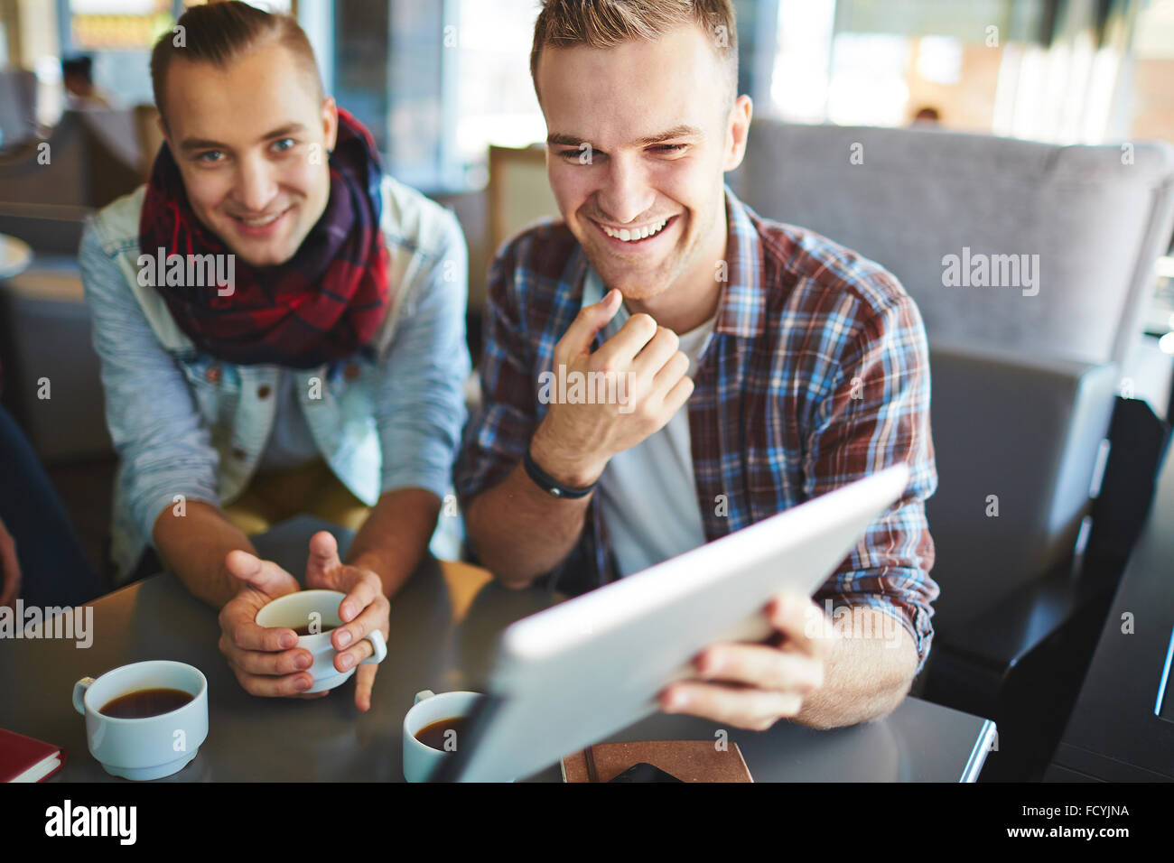 Friendly guys networking and drinking coffee in cafe - Stock Image