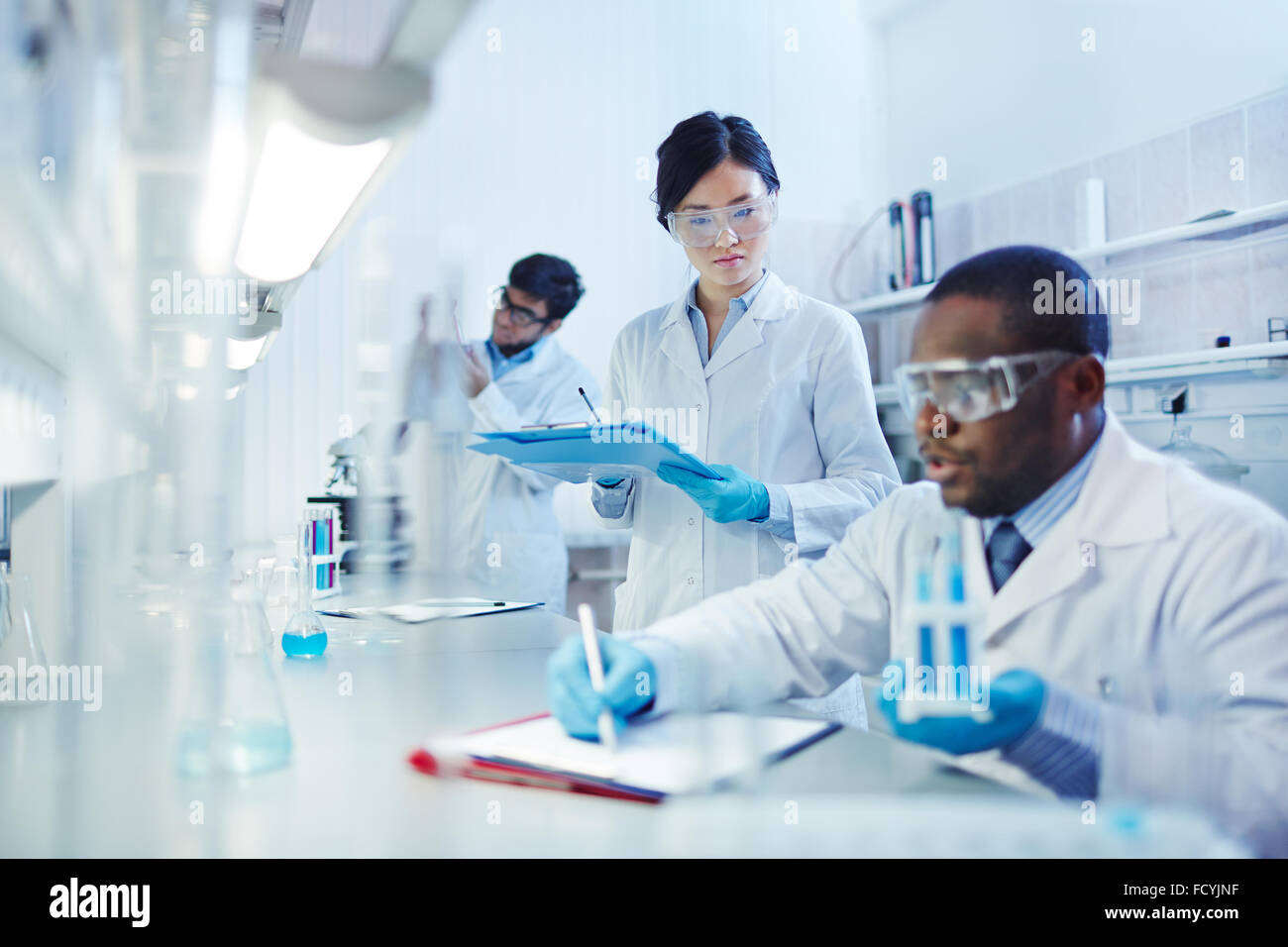 Young scientists analyzing substances in laboratory - Stock Image