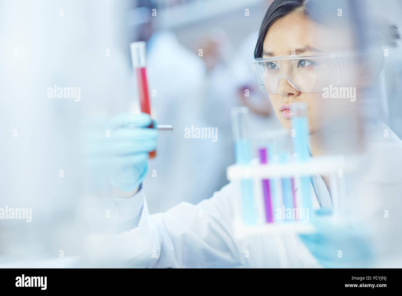 Young assistant analyzing substances in laboratory - Stock Image