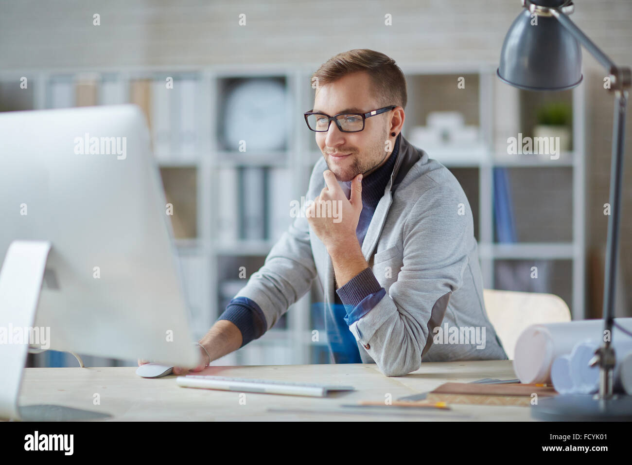 Young businessman in eyeglasses networking in office - Stock Image