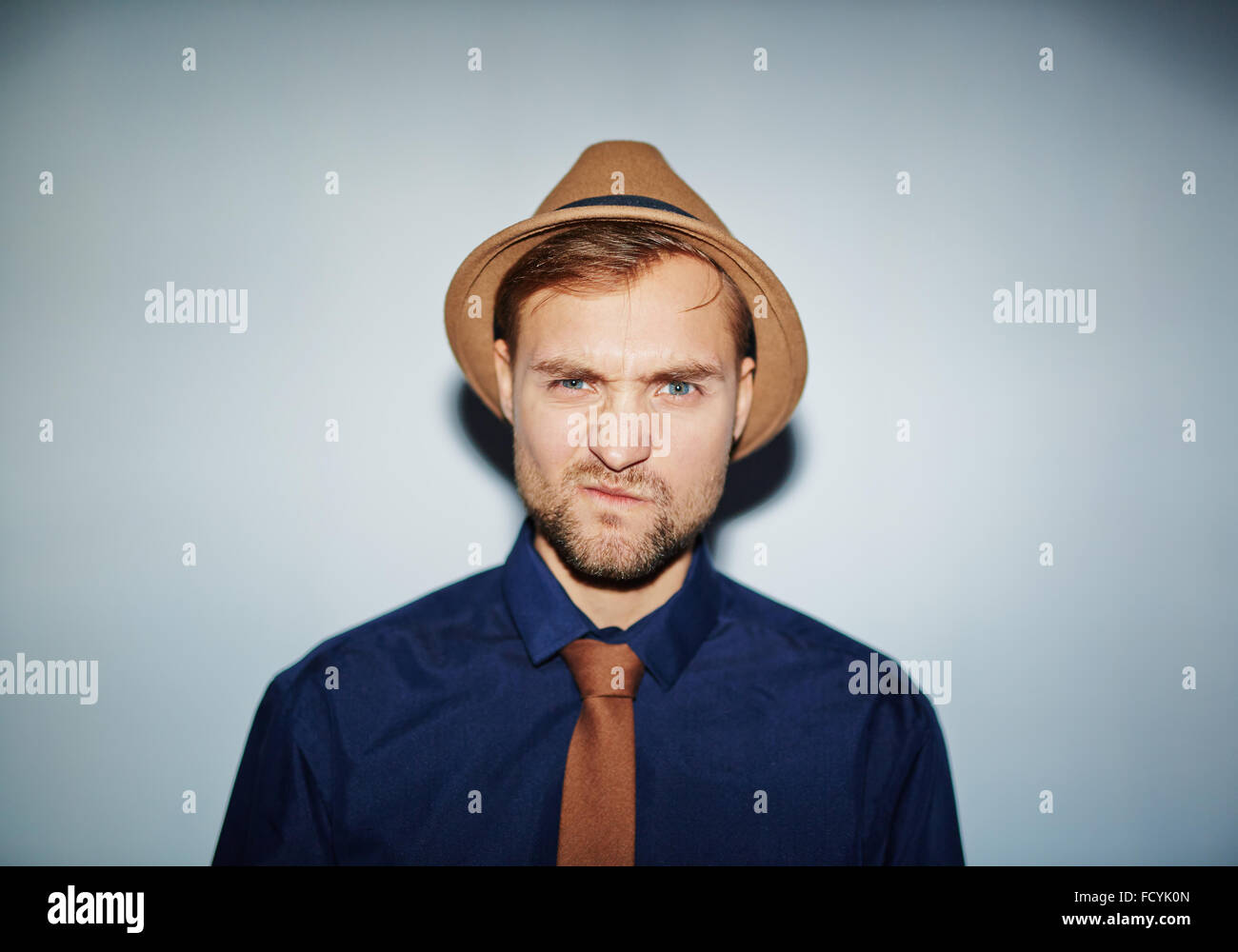 Confused or annoyed guy in hat, tie and shirt looking at camera - Stock Image