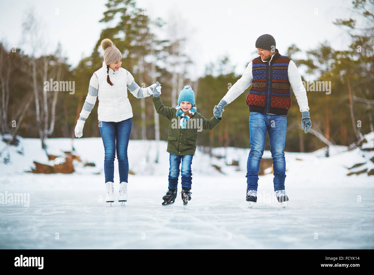 Family of three skating together on the rink at leisure - Stock Image