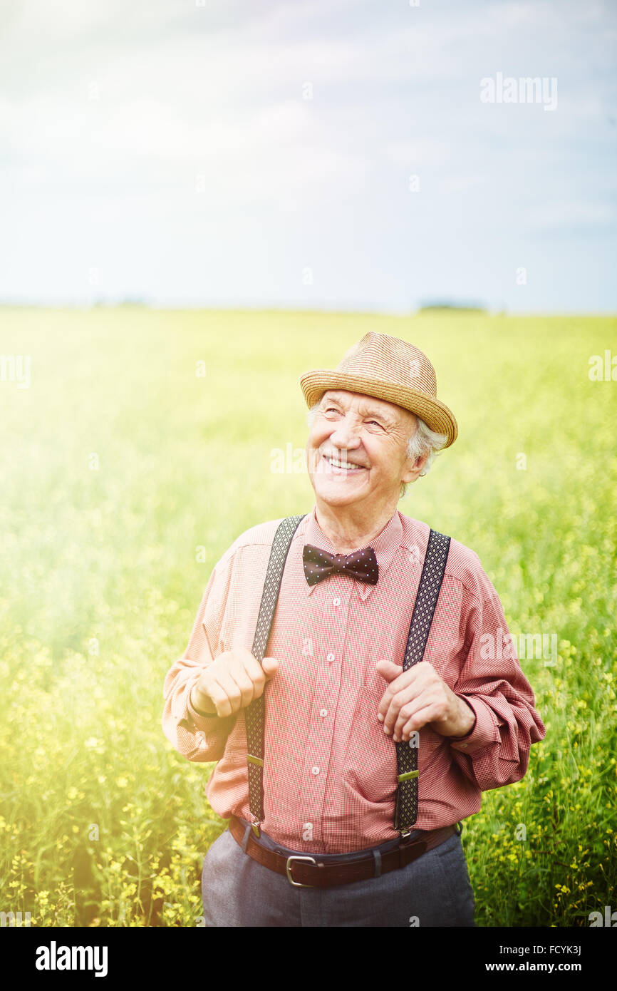 Well-dressed senior man standing in meadow - Stock Image