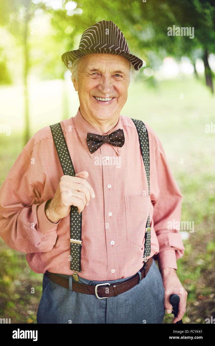 Senior man in hat, bowtie and shirt looking at camera in park - Stock Image
