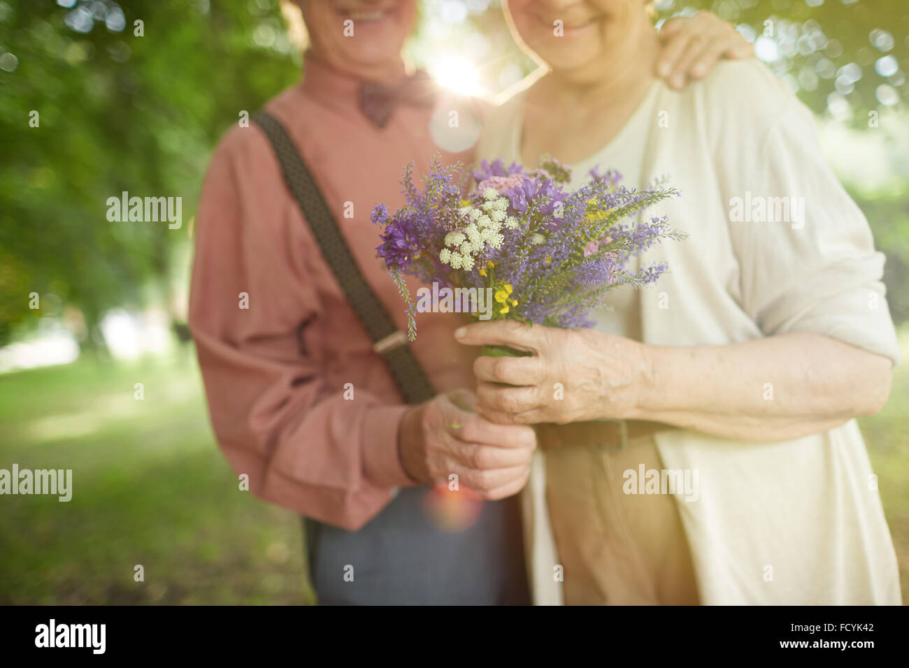 Romantic bouquet in hands of senior valentines - Stock Image