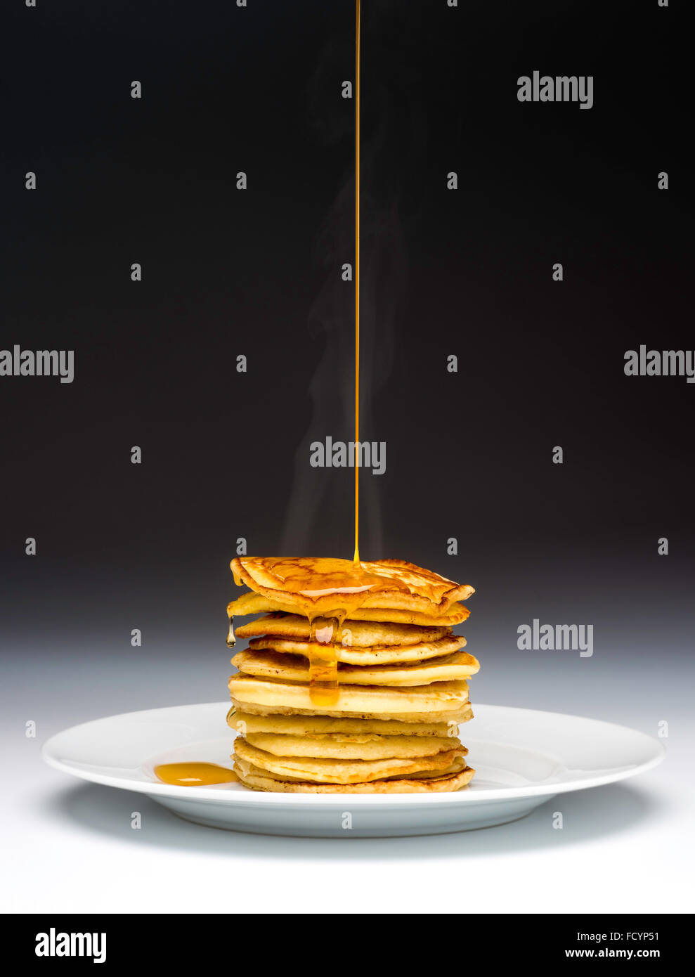 Stack of pancakes on white plate drizzled with syrup Stock Photo