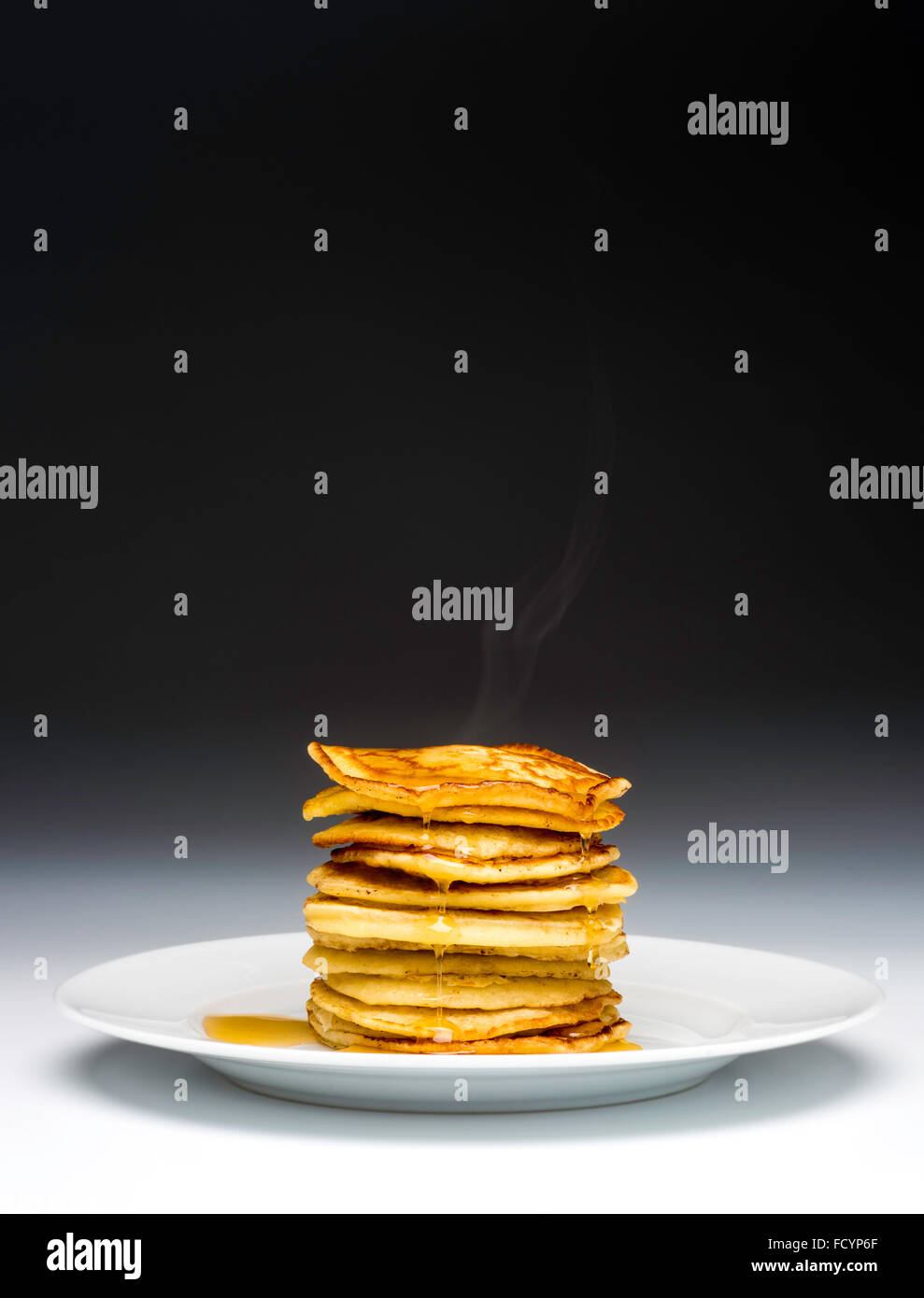 Stack of pancakes on white plate drizzled with syrup - Stock Image