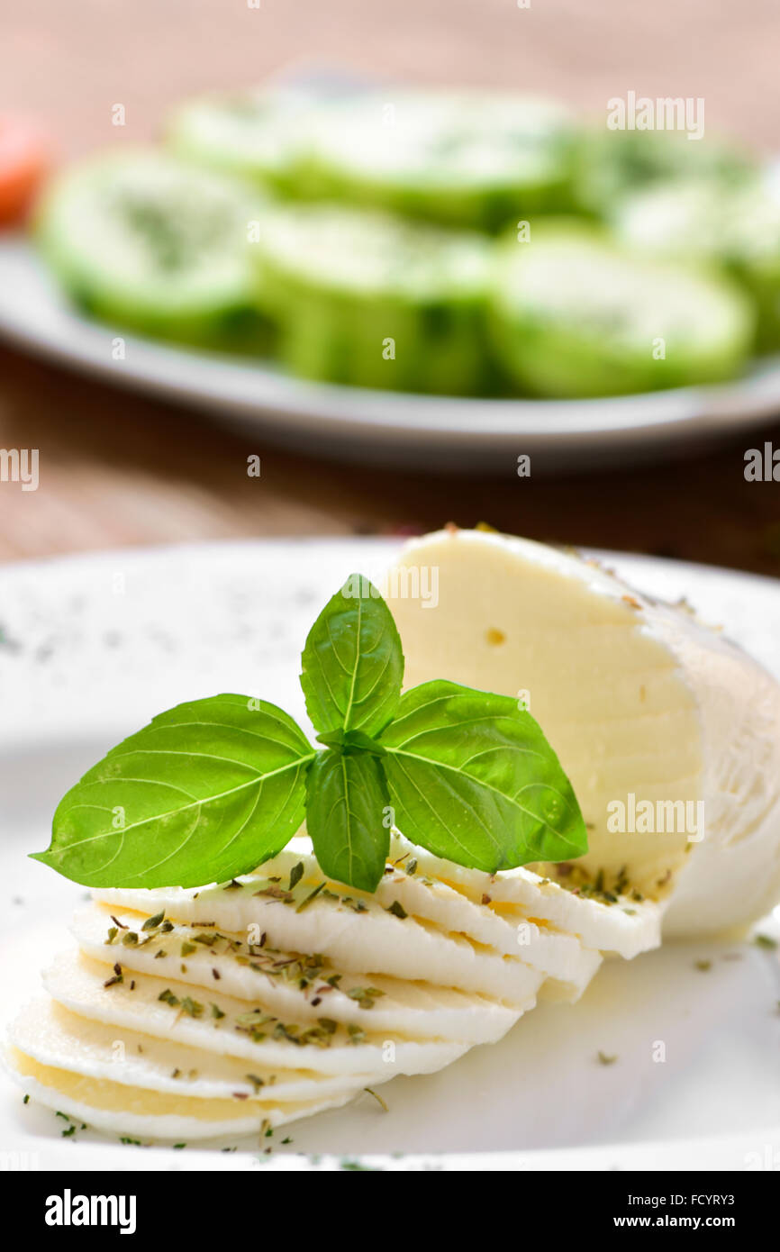 closeup of a plate with a sliced fresh cheese on a table, and a plate with chopped courgette in the background - Stock Image