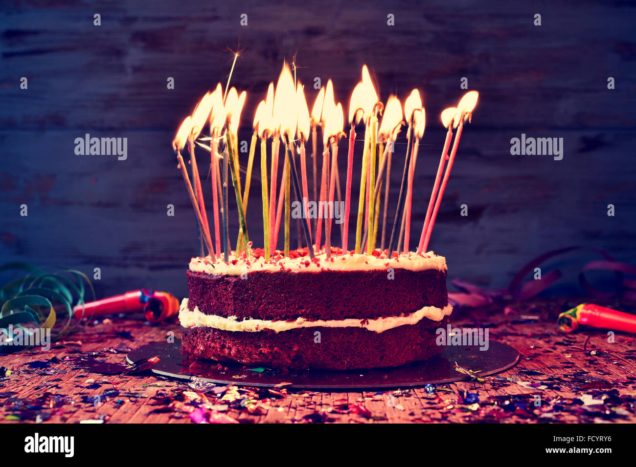 a cake topped with some lit candles before blowing out the cake, on a rustic wooden table full of confetti, party - Stock Image