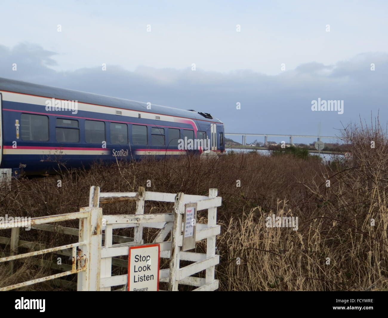 A Scot Rail train heads into Inverness just after crossing the Caledonian Canal. - Stock Image