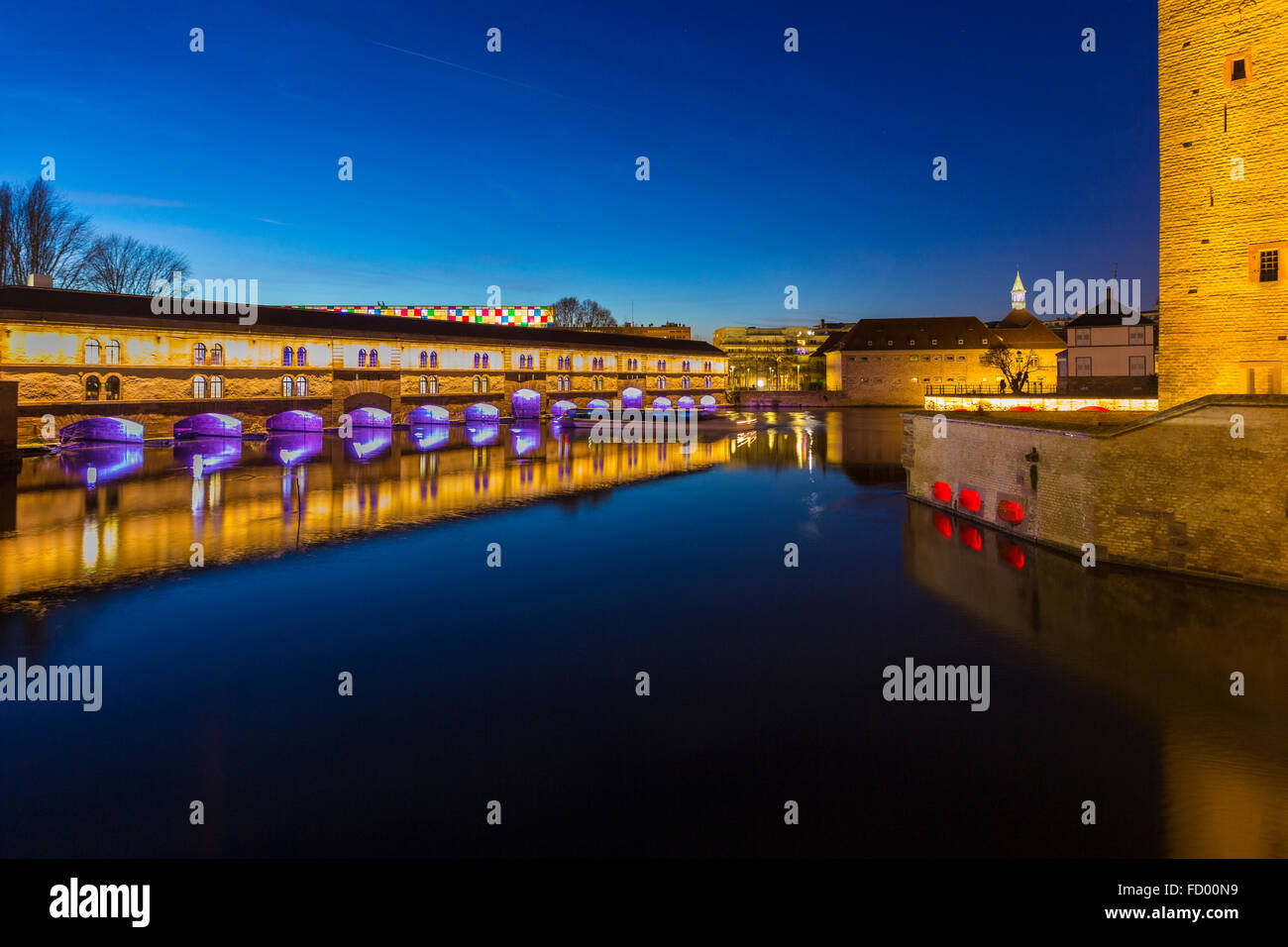 illumined Barrage Vauban at twilight reflected in the waters of the River Ill, Alsace France - Stock Image