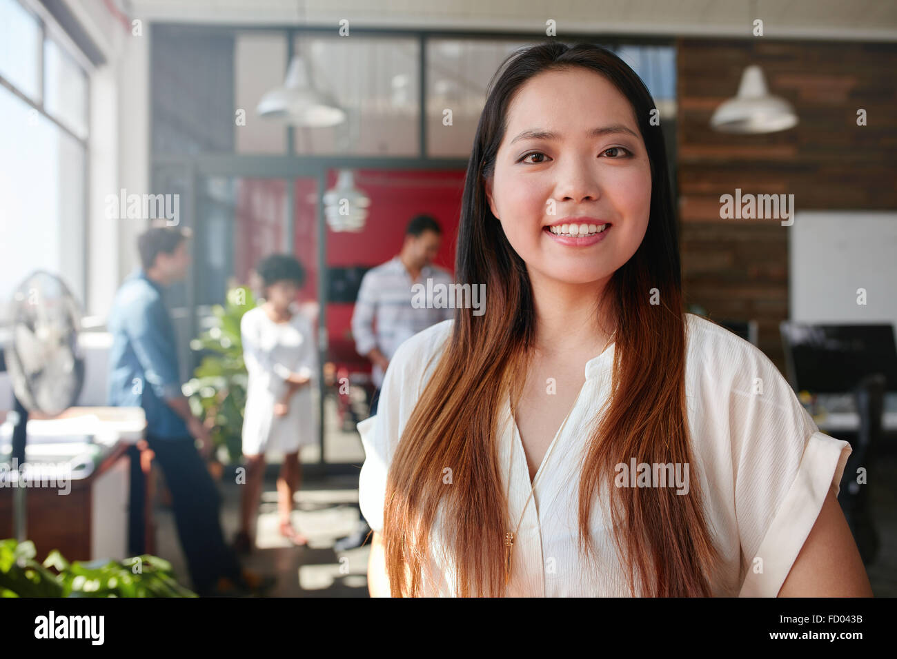 Smiling young businesswoman looking at camera and her colleagues are standing in the background. Young asian female - Stock Image