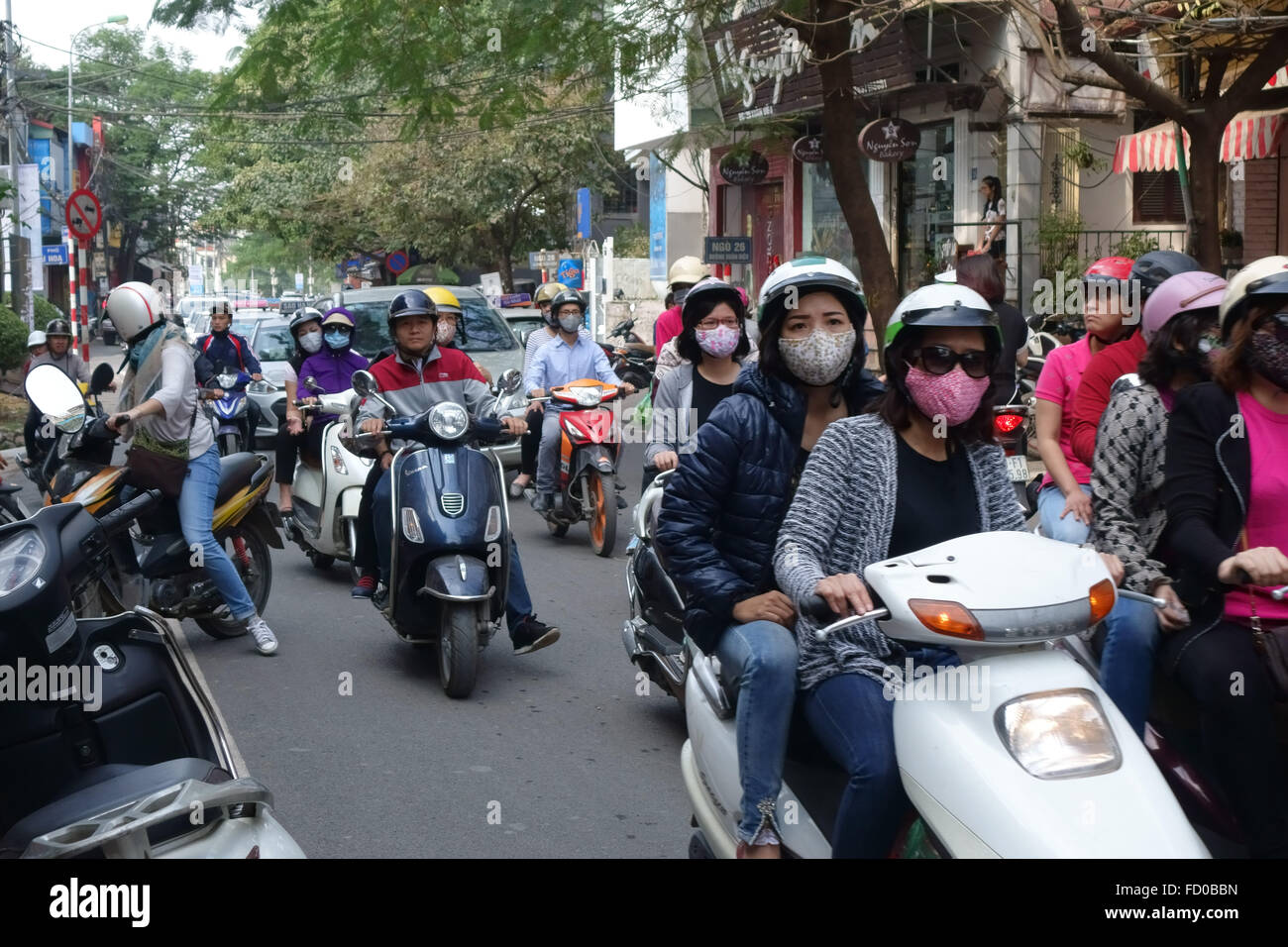 Scooters with riders, some wearing face masks, on a busy street in Hanoi, Vietnam - Stock Image
