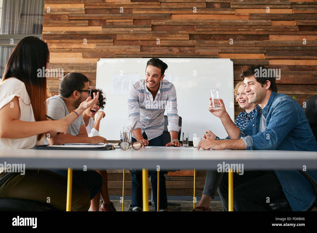 Group of happy young people having a business meeting. Creative people sitting at table in boardroom with man explaining - Stock Image