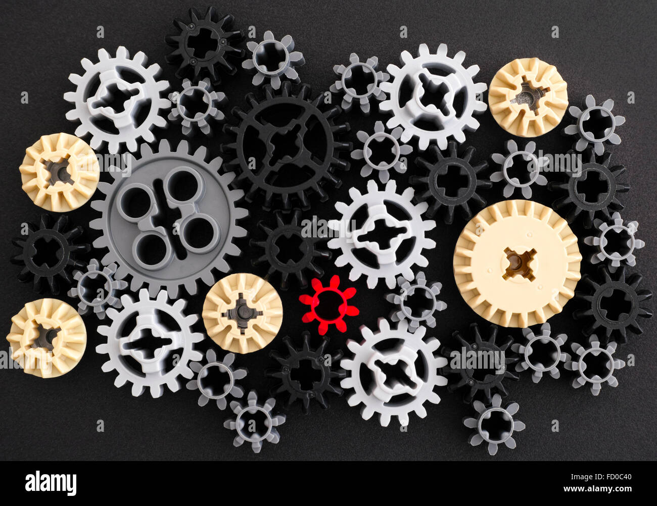 Plastic gears on black background - Stock Image