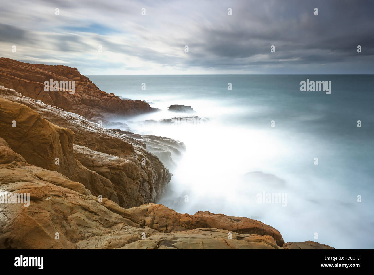Dark red rocks, waves and foam, ocean under cloudy sky in a bad weather. Long exposure photography. Livorno, Tuscany, - Stock Image