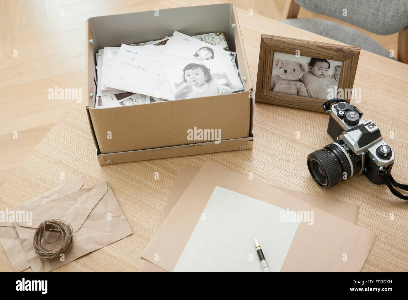 High angle of a  a box of old photos, photo frame, and a camera - Stock Image