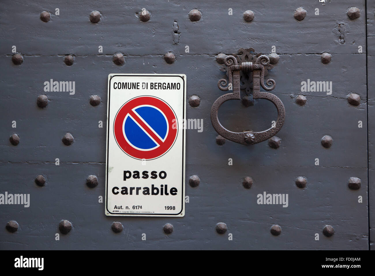 Old metal doorknocker and No Parking sign on the black painted wooden gate fixed with rivets in Bergamo, Lombardy, - Stock Image