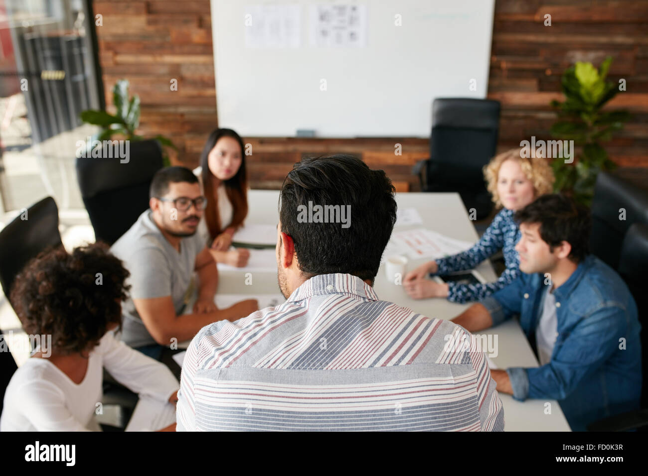 Rear view portrait of man explaining business plan to coworkers during a meeting in conference room.  Young people - Stock Image