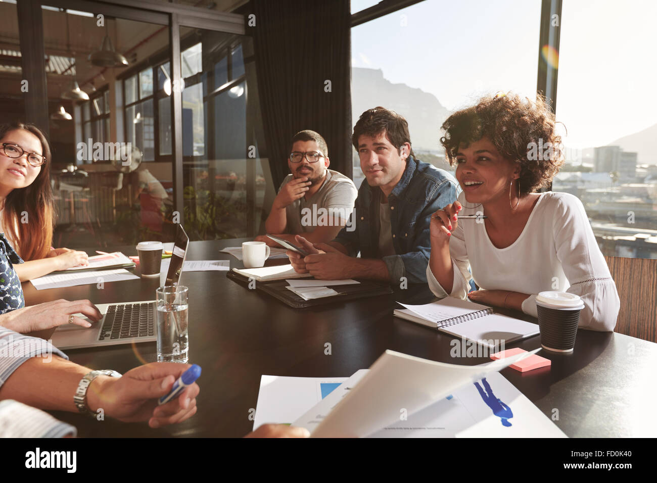 Team of young people discussing new business plan during a meeting in office. Mixed race team of designers discussing - Stock Image