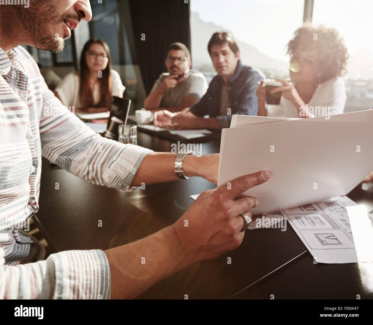 Closeup of hands of young man explaining business plan to colleagues. Creative people meeting in conference room. - Stock Image
