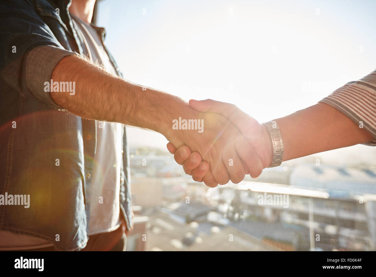 Closeup of two shaking male hands with sun flare. Focus on handshake against cityscape. - Stock Image