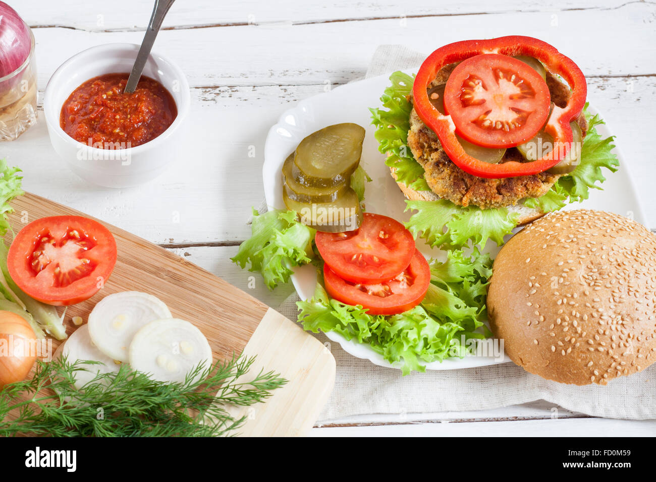 Homemade hamburger on white plate, sliced tomatoes, onion, pepper, lettuce and dill on wooden board, tomatoes souse - Stock Image