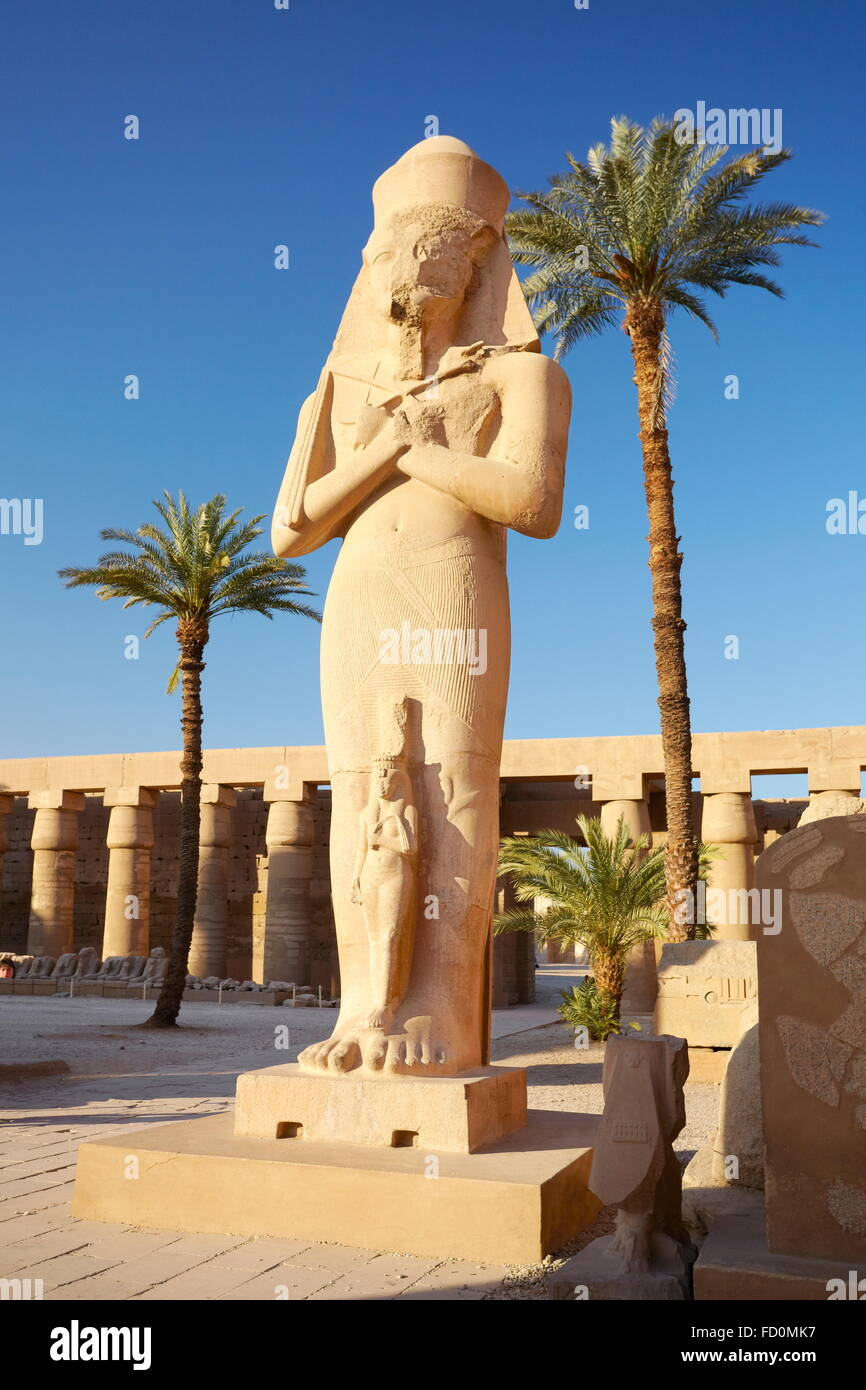 Karnak, Egypt - Statue of Pharaoh Ramses II with Queen Nefertari in the Great Courtyard, Amun-Re Temple Stock Photo