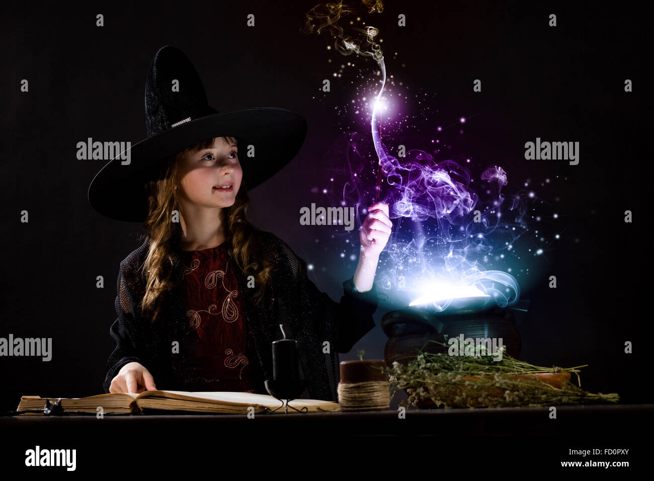 Little Halloween witch reading conjure above pot - Stock Image
