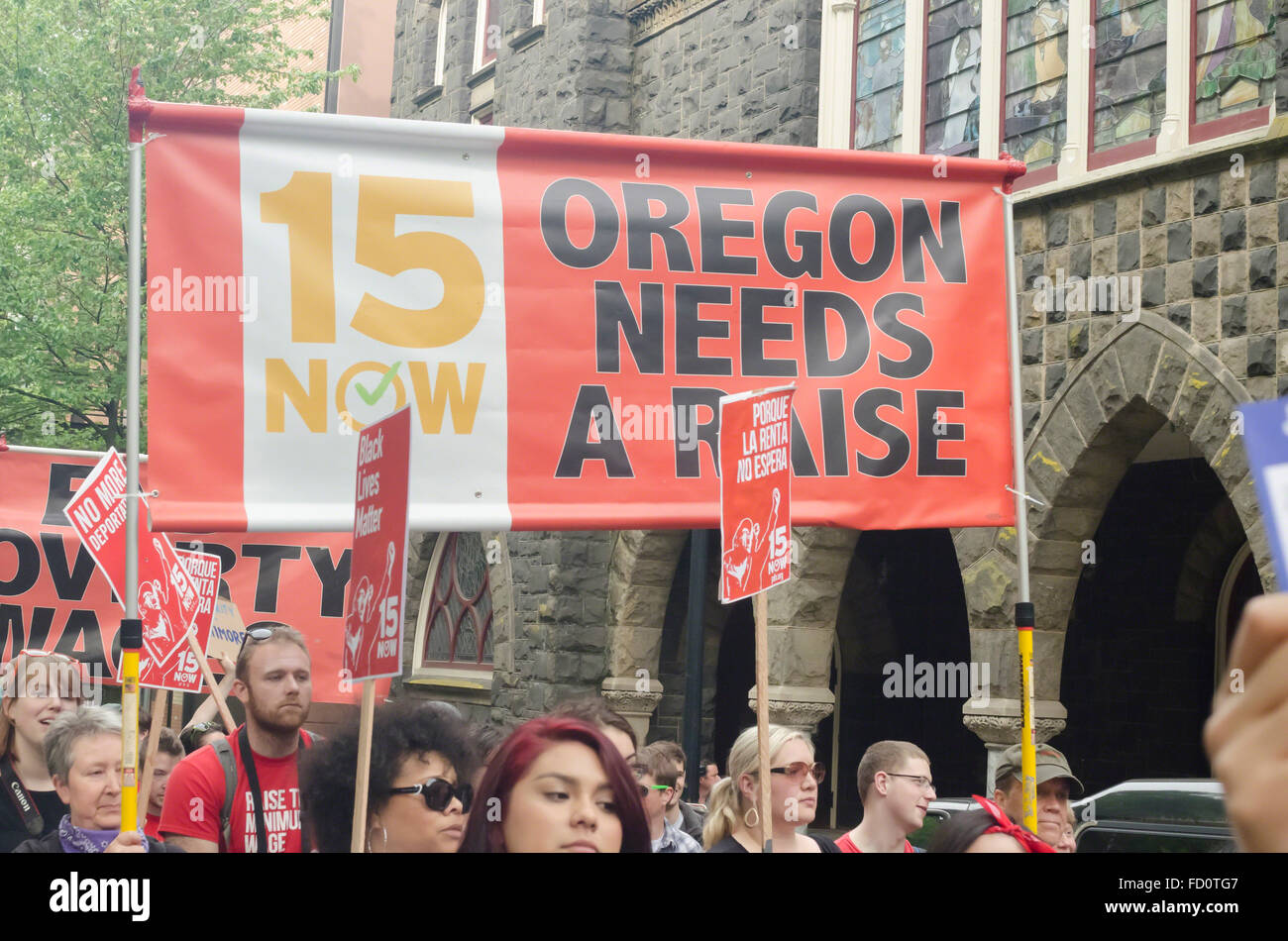 Demonstrator in 2015 May Day rally in Portland, Oregon hold a banner supporting a state-wide minimum wage increase - Stock Image