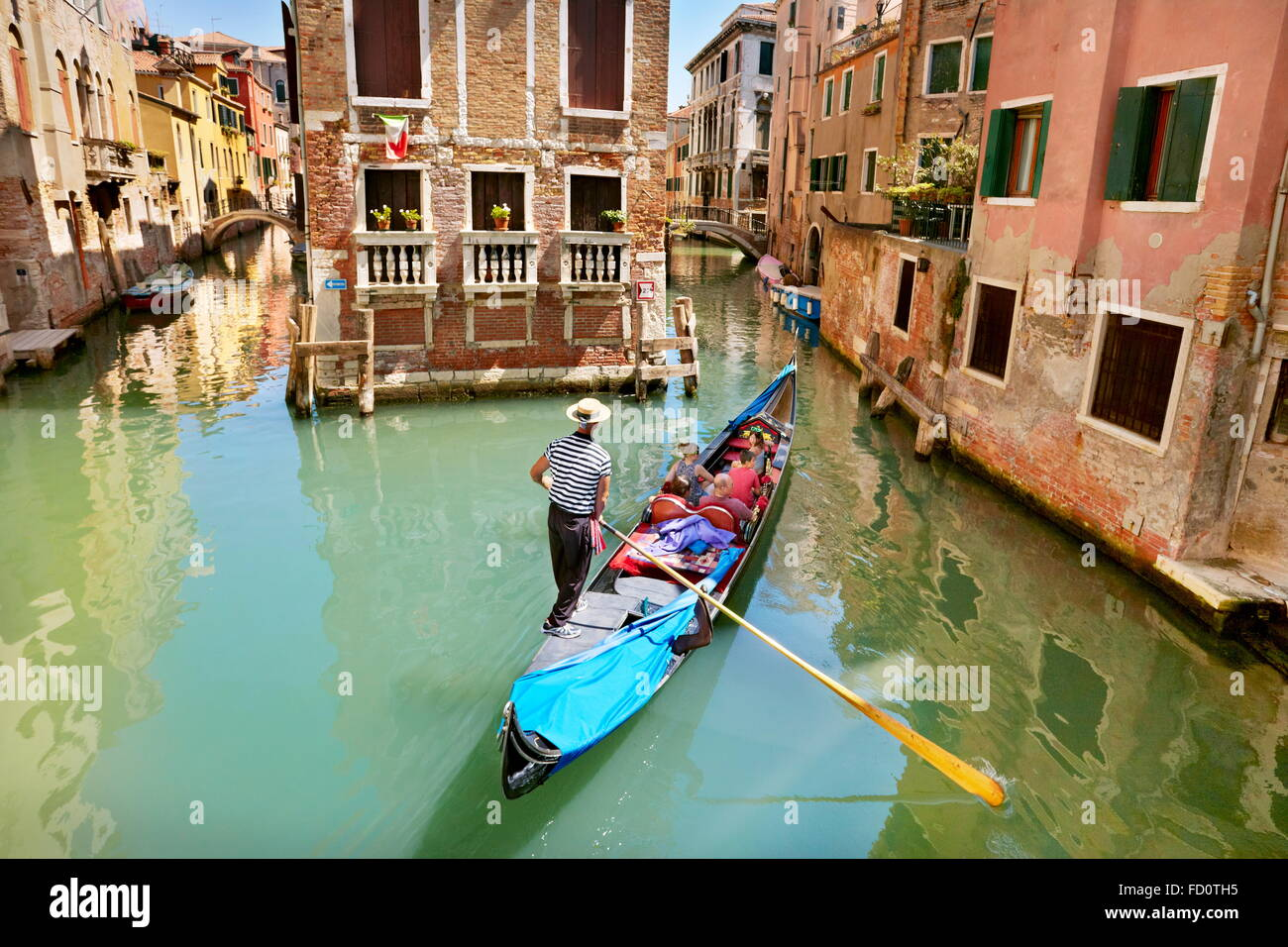 Gondolier with his gondola in one of the numerous canals Venice, Veneto, Italy, UNESCO - Stock Image