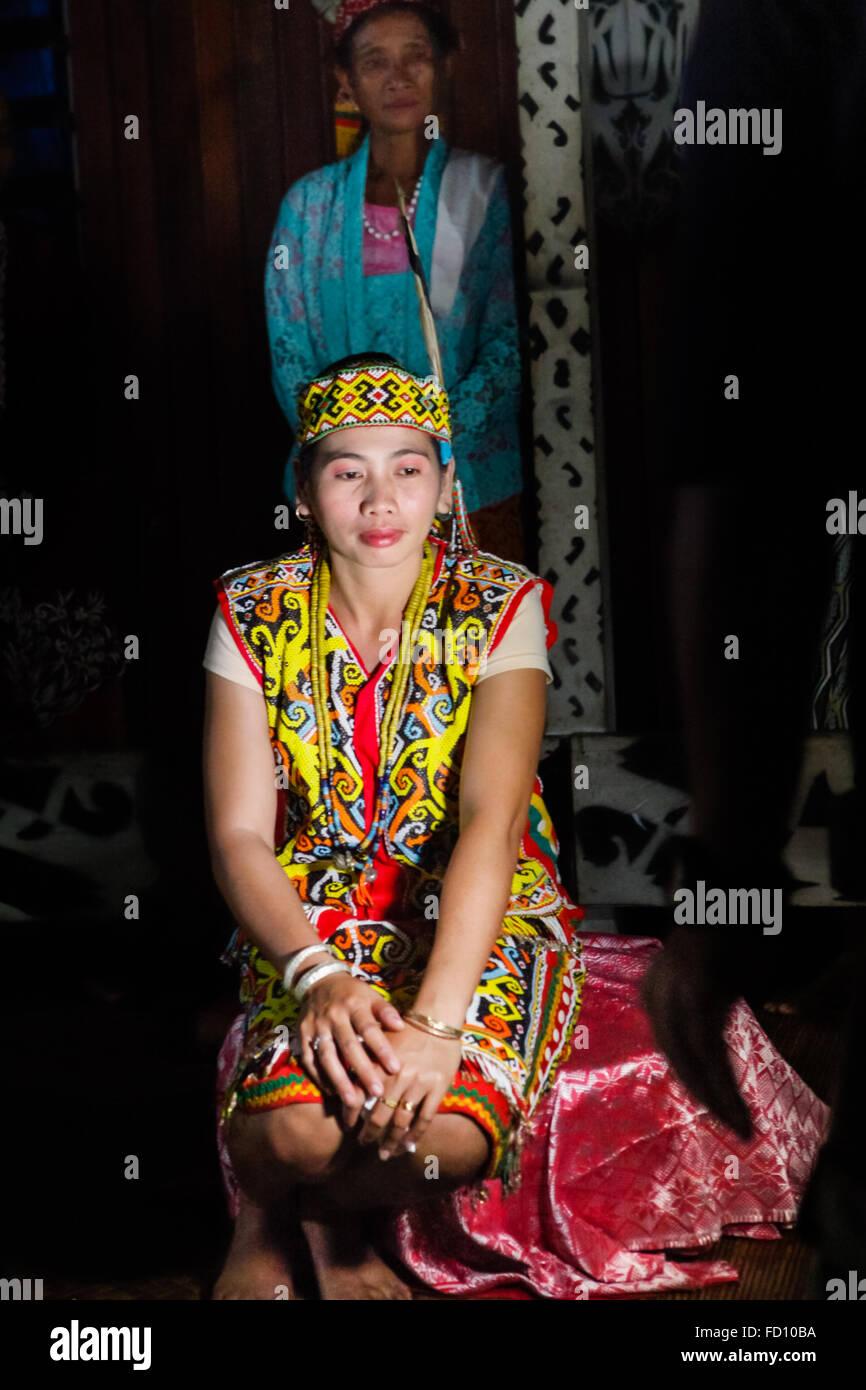 Portrait of a young woman inside Bali Gundi longhouse in West Kalimantan, Indonesia. © Reynold Sumayku - Stock Image