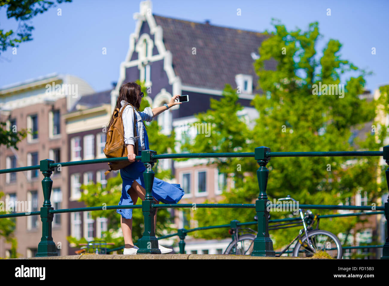 Young woman taking self portrait in european city outdoors. Young adult  holding smartphone camera to take a picture of herself during her summer  vacation in ...