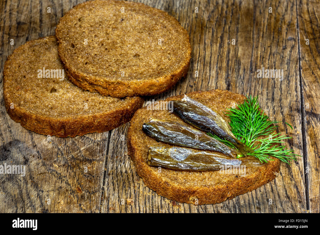 Rye bread with delicious anchovies on old wooden table - Stock Image