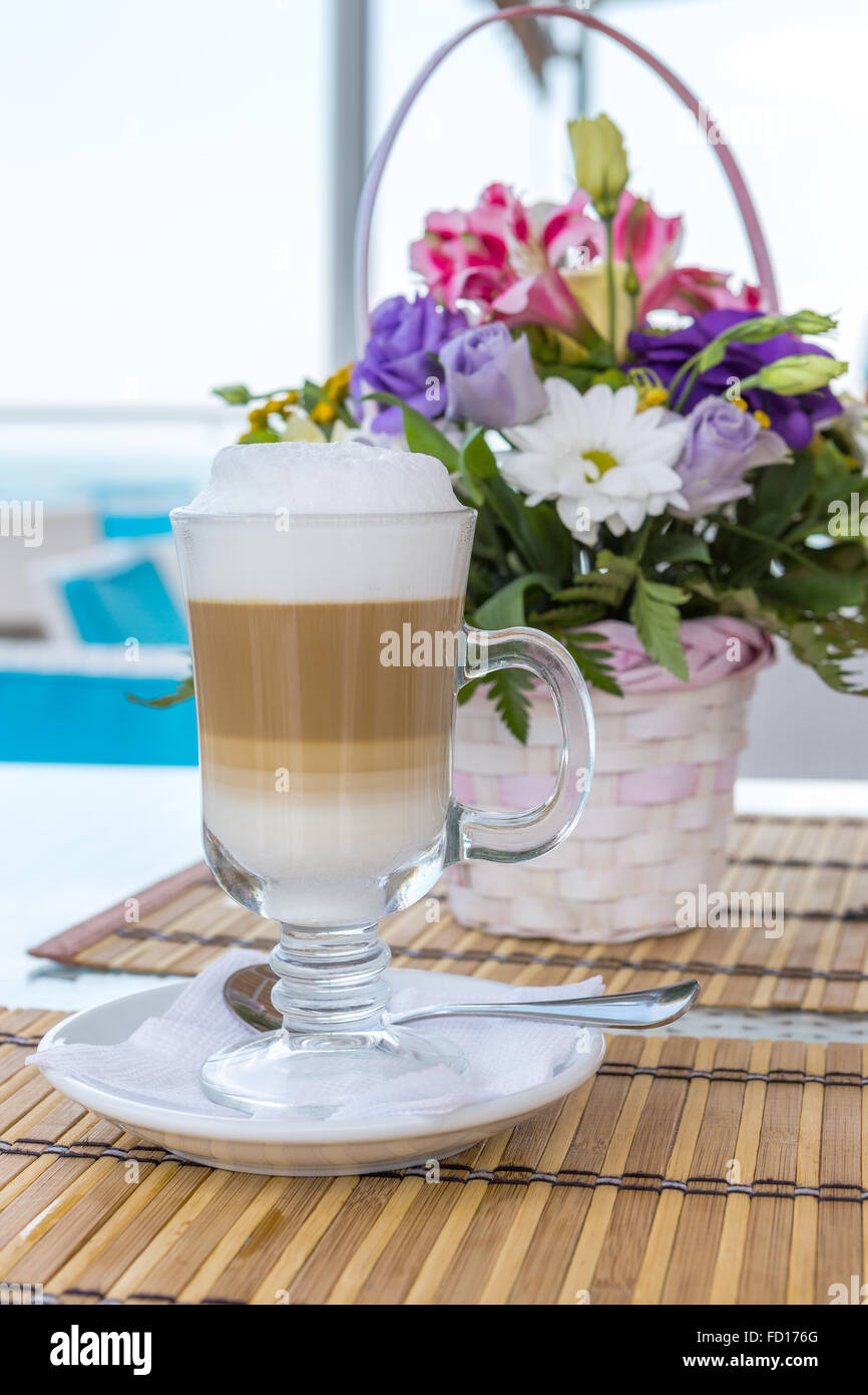 Latte in a glass with a blurred background of a beautiful bouquet of flowers - Stock Image