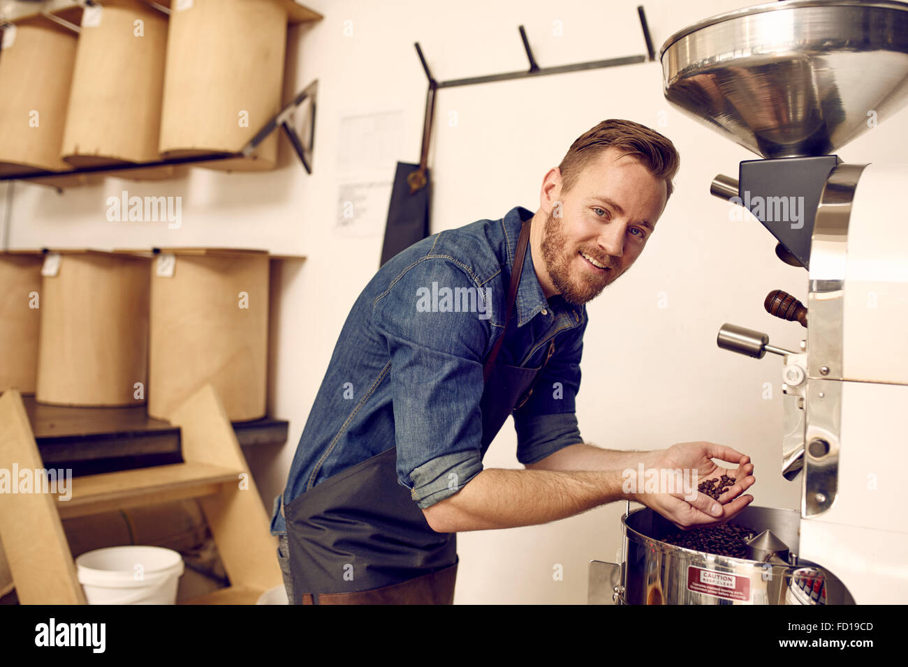 Coffee expert checking freshly roasted coffee beans in modern ma - Stock Image