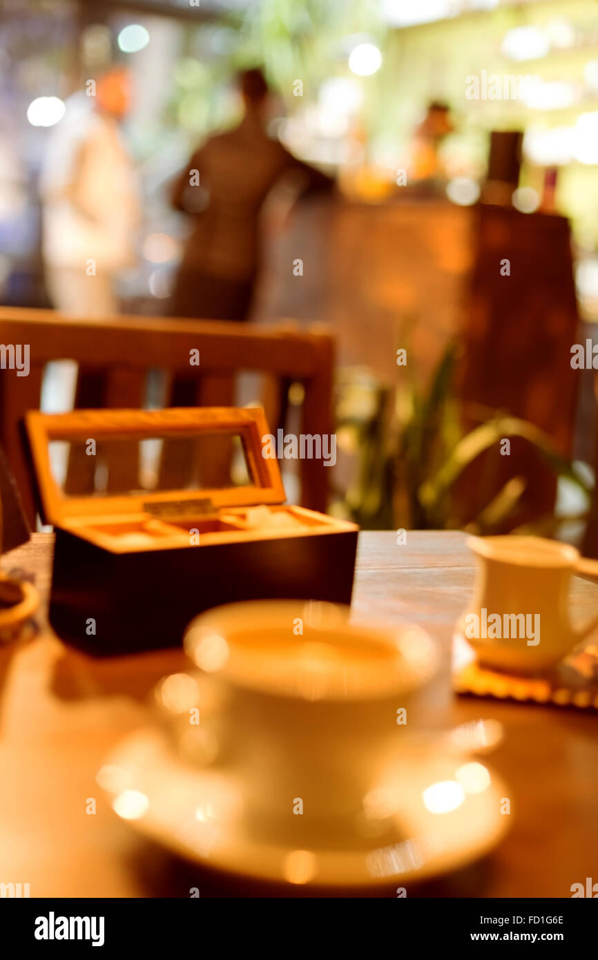 cup of coffee, an evening cafe blurred background in warm colors - Stock Image