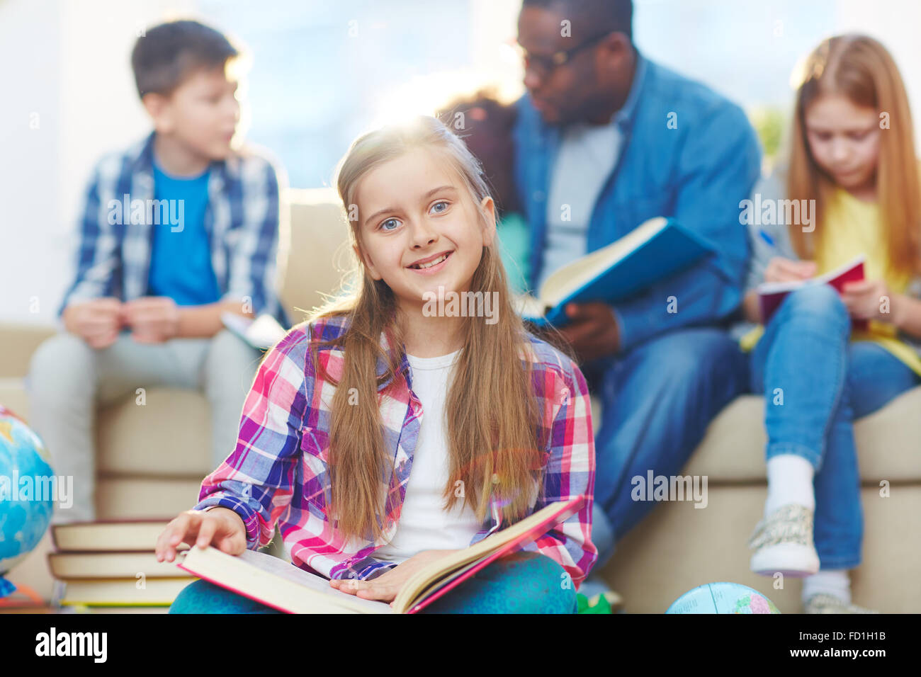 Pretty schoolgirl looking at camera on background of other pupils and their teacher - Stock Image