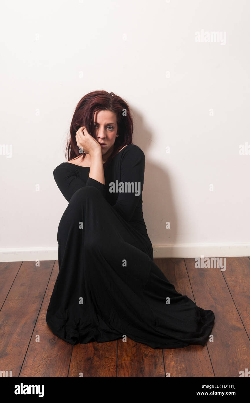 Depressed woman sat on the floor - Stock Image