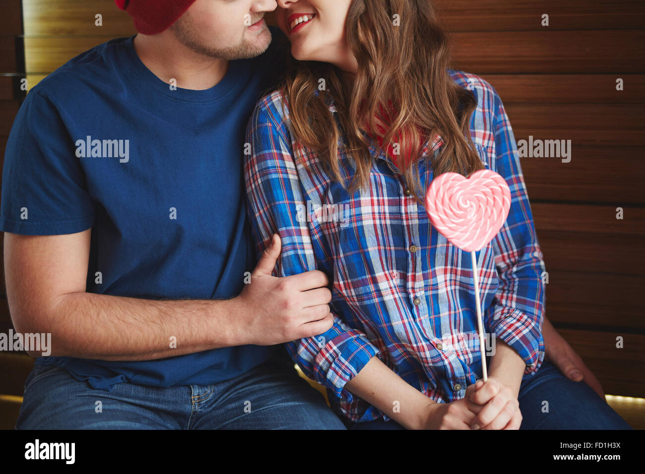 Amorous woman with heartshaped candy flirting with young man - Stock Image