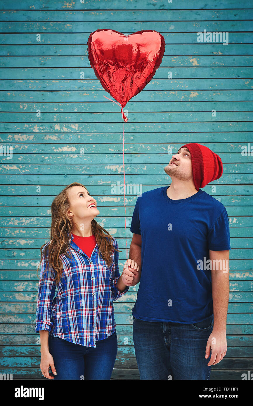 Young couple looking at red heart-shaped balloon - Stock Image