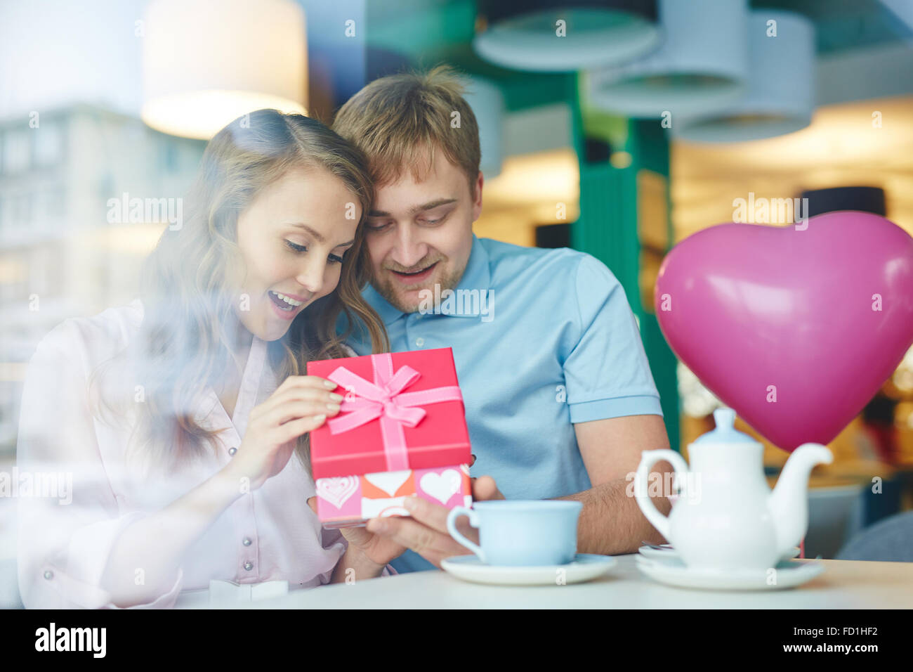 Young surprised woman opening her boyfriend gift in cafe - Stock Image