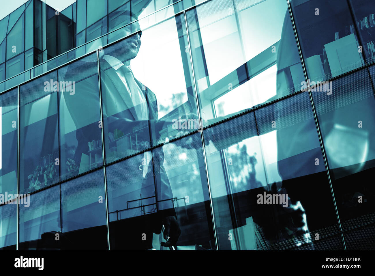 Confident businessman greeting his partner and exterior of modern office building - Stock Image