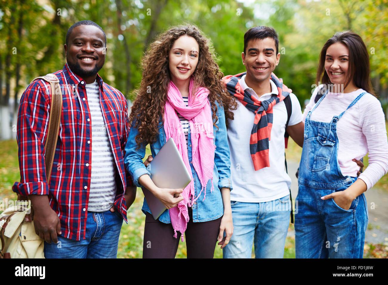 Joyful college friends in casualwear standing outside - Stock Image