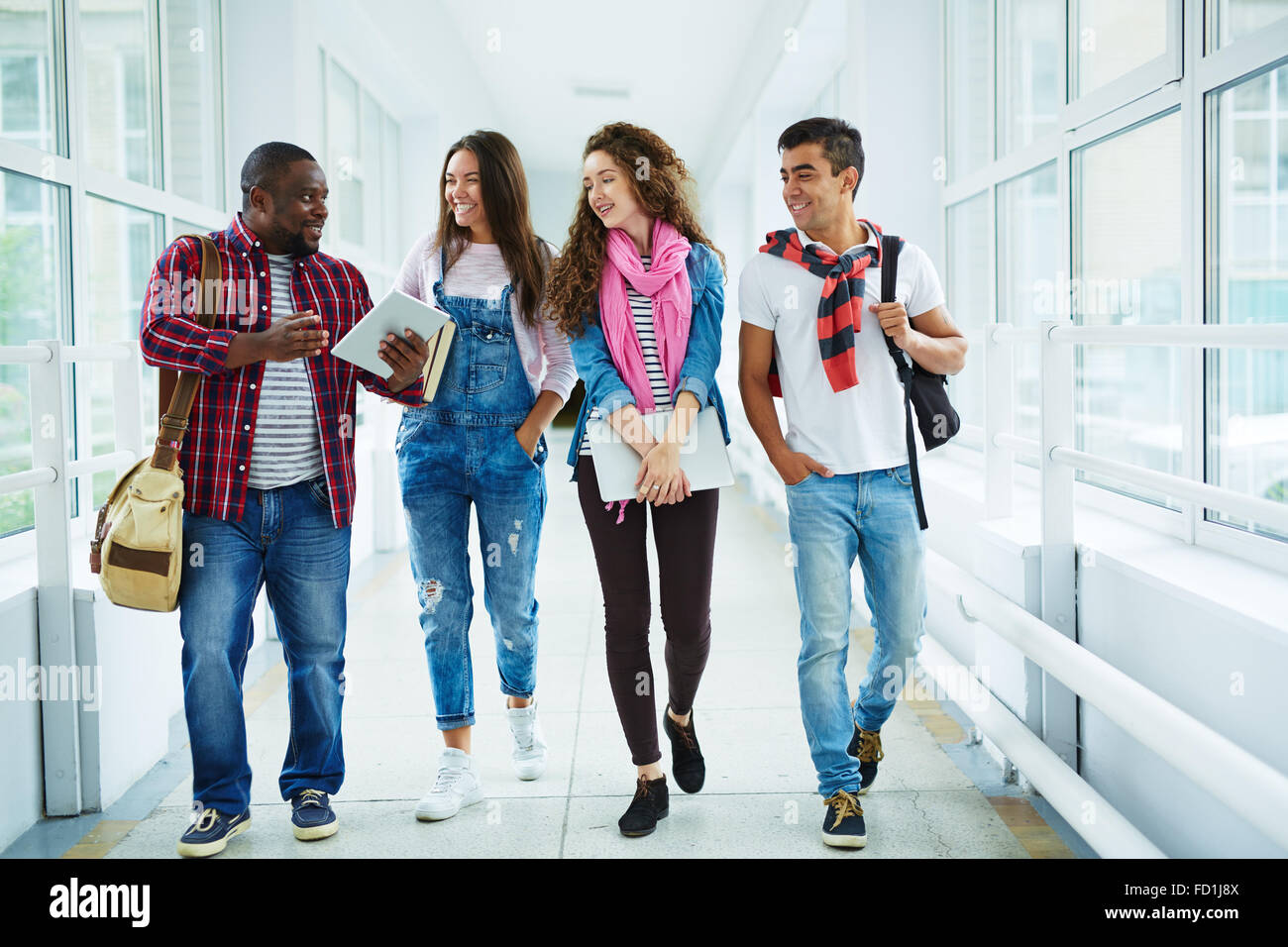 Happy high school learners walking down college corridor and chatting during break - Stock Image