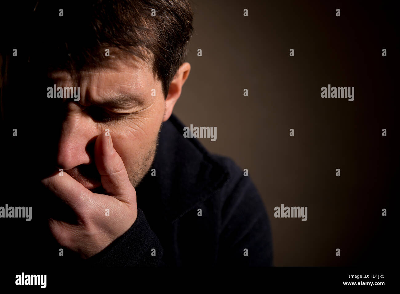 Portrait of man crying, with one hand over his mouth and eyes closed with pain. His face spot lit with half his - Stock Image